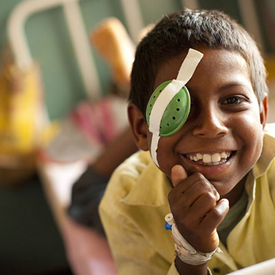 Young boy with eye cover, smiling