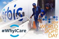 Volunteer escorting patient off Orbis plane - World Sight Day