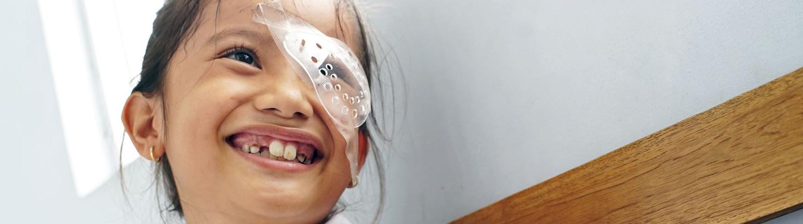 Young girl smiling, wearing eyepatch