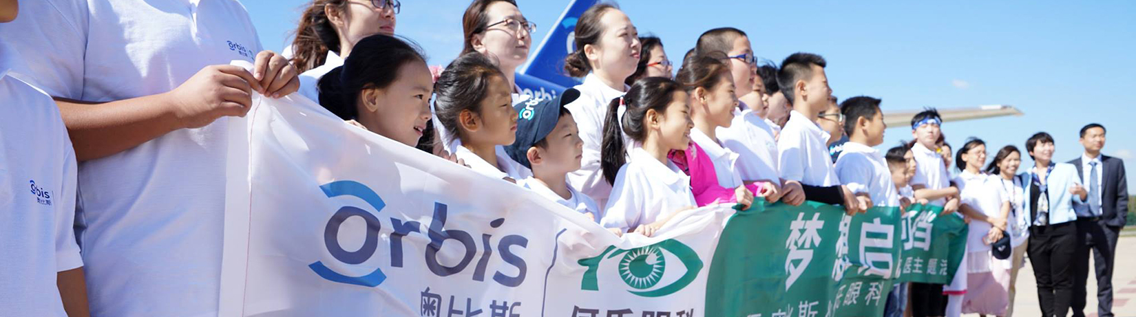 Young children holding Orbis banner at event